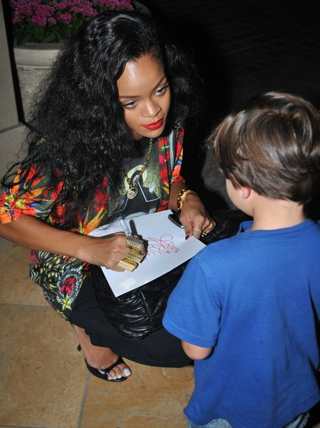 Rihanna signs an autograph for young boy