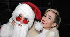 Miley Cyrus poses with Santa